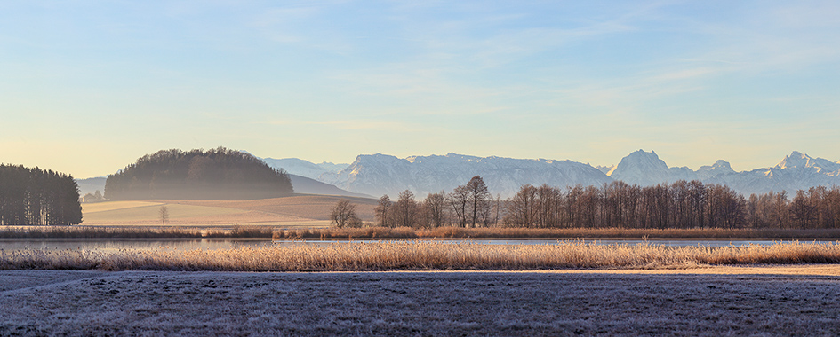 Hügellandschaft mit See vor Bergkette, Foto: Andreas Mühlleitner